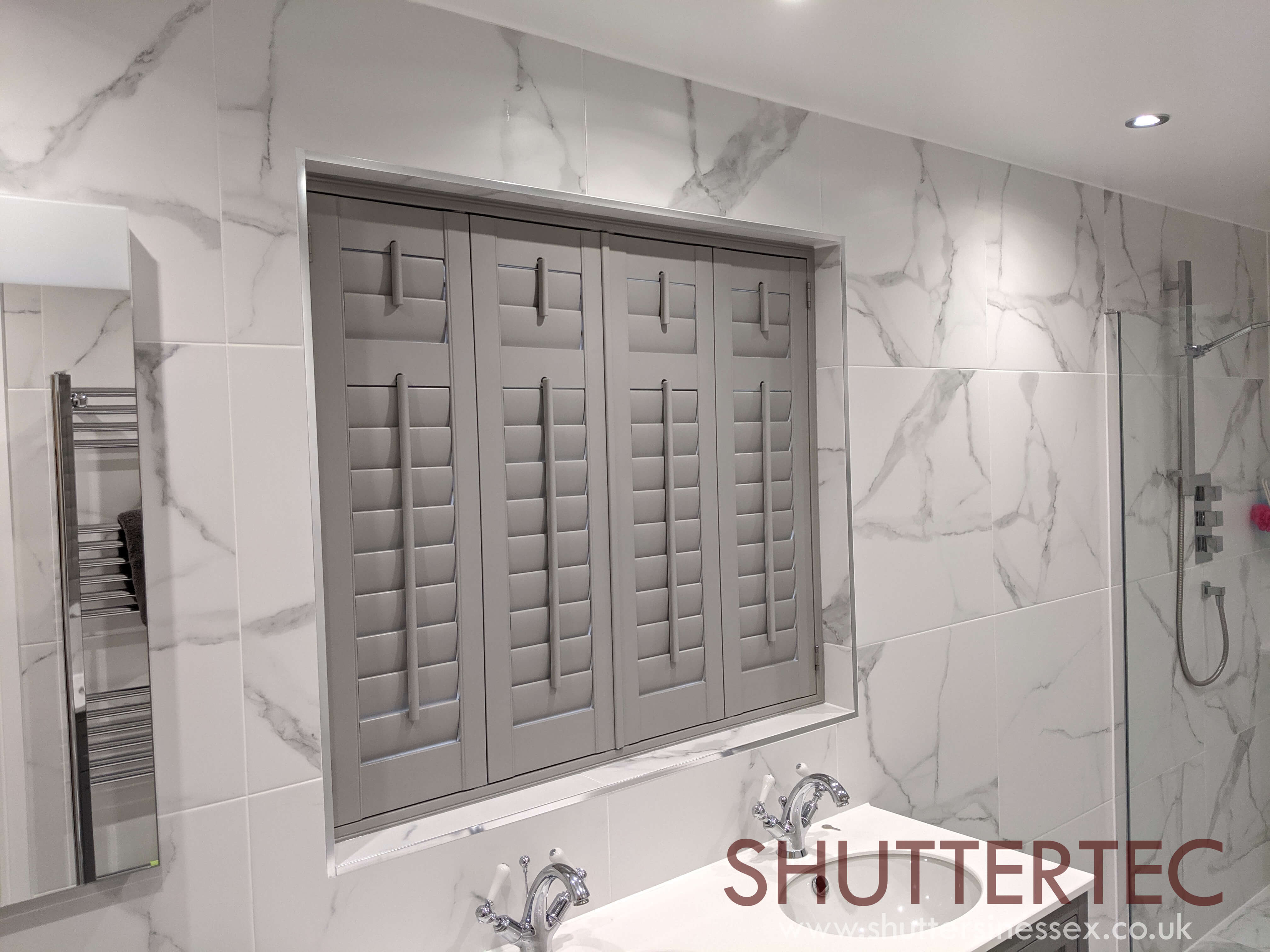 image of closed shutters in a bathroom for blog by Shuttertec on whether shutters are warmer than curtains